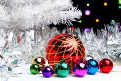Weißer Weihnachtsbaum, der im funkelnden Lametta mit Weihnachtsdekorationen auf dunklem Hintergrund mit unscharfen Lichtern steht Lizenzfreie Stockfotografie