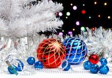 Weißer Weihnachtsbaum, der im funkelnden Lametta mit Weihnachtsdekorationen auf dunklem Hintergrund mit unscharfen Lichtern steht Stockbild