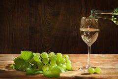 Weißer Wein, der unten zum Glas mit Trauben gießt Lizenzfreies Stockfoto