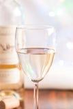 Weißer Wein des Glases und der Flasche auf Blinken beleuchten Lizenzfreies Stockfoto