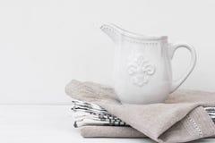 Weißer Weinlesepitcher auf einem Stapel Leinentüchern, angeredetes Bild mit copyspace für Produkt-Marketing Lizenzfreie Stockbilder