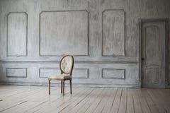 Weißer Weinlesestuhl, der vor einer hellen Wand mit Formteilen auf hölzernem Parkettboden steht Stockfotos