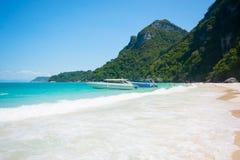 Weißer Wellenschaum auf breitem Strand an der Inselküste im sonniger Tagesblauen Himmel Lizenzfreies Stockbild