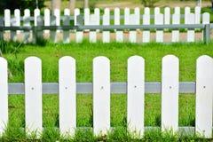 Weißer Zaun um den Rasen im Garten Lizenzfreie Stockfotos