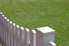 Weißer Zaun und grünes Gras des Hauses Stockbilder