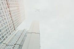 Weißer zeitgenössischer Wohnwolkenkratzer mit einem Fliegenflugzeug stockfotografie