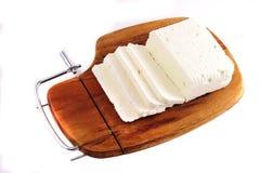 Weißer Ziegekäse und -scheibe auf hölzerner Platte Stockbild