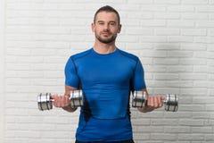 Weißer Ziegelstein-Hintergrund persönlicher Trainer-Exercising Biceps Ons lizenzfreie stockfotografie