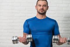 Weißer Ziegelstein-Hintergrund persönlicher Trainer-Exercising Biceps Ons stockbilder