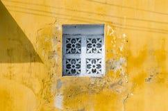 Weißes altes Weinlesefenster auf der gelben Wand Stockfotografie