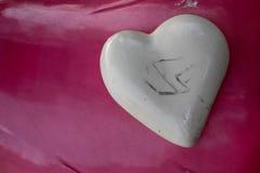 Weißes ausbauchendes prägeartiges Herz auf hellem glattem hochrotem Hintergrund, ein Symbol der Liebe Stockbild