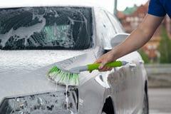 Weißes Auto wird von einer Reinigungsarbeitskraft gewaschen, die mit einer grünen Bürste Hand ist stockfotografie