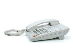 Weißes Bürotelefon mit dem Hörer bei aufliegendem Hörer Lizenzfreies Stockfoto