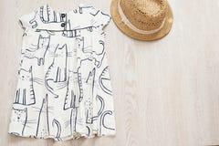Weißes Babykleid und -strohhut auf einem hellgrauen hölzernen Hintergrund Babysommermode-accessoires Draufsicht, Kopienraum Lizenzfreies Stockbild