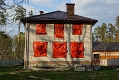 Weißes Backsteinhaus mit roten Fenstern im Yard Stockfotos