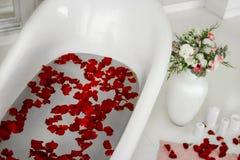 Weißes Bad mit den rosafarbenen Blumenblättern Nehmen eines Bades mit Rosen stockbild