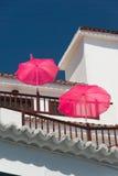 Weißes Balkonhaus mit rosa Sonnenschirmen auf einem Hintergrund des blauen Himmels Stockbilder