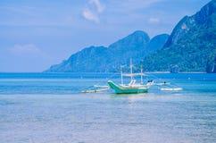 Weißes banca Boot im ruhigen blauen Ozean, sieben Kommandos setzen im Hintergrund, EL Nido, Philippinen auf den Strand Stockfoto