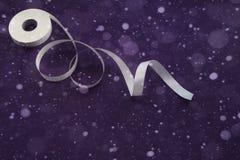 Weißes Band für dekorative Feiertagsdekoration auf purpurrotem Hintergrund Lizenzfreies Stockbild