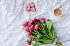 Weißes Bett mit Blumenstrauß von Tulpen lizenzfreie stockfotos