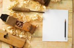 Weißes Blatt auf Holztisch für Tischlerwerkzeuge mit Sägemehl Lizenzfreie Stockfotos