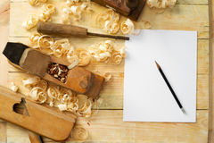 Weißes Blatt auf Holztisch für Tischlerwerkzeuge mit Sägemehl Stockfotos