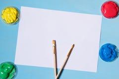 Weißes Blatt Papier auf einem blauen Hintergrund, farbigen roten einer Gelbfarbe des blauen Grüns und einem Bürstenplatz für den  Stockfotografie