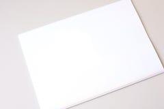 Weißes Blatt Papier auf weißem Hintergrund Stockbild