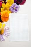 Weißes Blatt Papier umgeben mit bunten Blumen lizenzfreie stockfotos