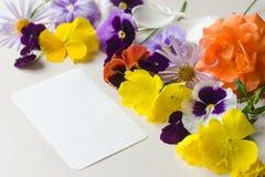 Weißes Blatt Papier umgeben mit bunten Blumen lizenzfreie stockbilder