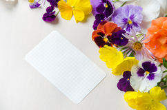 Weißes Blatt Papier umgeben mit bunten Blumen lizenzfreies stockfoto