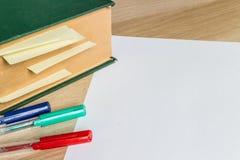Weißes Blatt Papier und großes Buch mit markierten Seiten stockfoto
