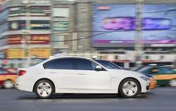 Weißes BMW 5 Reihe im beschäftigten Stadtzentrum, Peking, China Stockfotografie