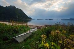 Weißes Boot auf dem Ufer mit Ansicht zum Berg und zum Meer im Norwegen am Sommer Stockfotografie