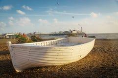 Weißes Boot auf einem Pebble Beach Stockfotos