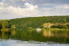 Weißes Boot, das hinunter den Fluss auf einem Waldhintergrund schwimmt Lizenzfreie Stockfotos