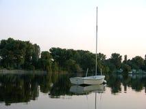 Weißes Boot, das in Wasser sich reflektiert Stockbilder