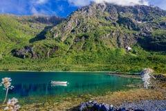 Weißes Boot im See mit Ansicht zu den Bergen im Norwegen am Sommer Stockbilder