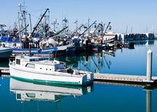 Weißes Boot mit grüner Ordnung auf ruhigem blauem Wasser Stockfotos
