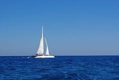 Weißes Boot mit Segeln im Mittelmeer Stockbilder