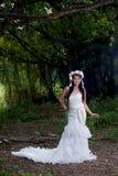 Weißes Brautkleid schöner asiatischer Dame, werfend im Wald auf Stockbild
