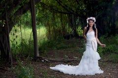 Weißes Brautkleid schöner asiatischer Dame, werfend im Wald auf Stockfoto