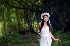 Weißes Brautkleid schöner asiatischer Dame, werfend im Wald auf Stockfotografie
