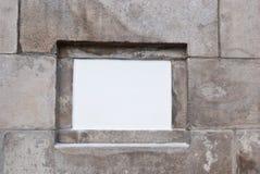 Weißes Brett auf Backsteinmauer Stockbilder