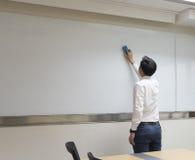 Weißes Brett des Geschäftsmann-Staubtuchs im Konferenzzimmer Lizenzfreies Stockfoto