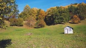Weißes Bretterbude-Haus auf einem Feld mit Bäumen im Fall/im Herbst Lizenzfreies Stockbild