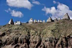 Weißes buddhistisches tibetanisches altes stupa auf dem Kamm des hohen Berges unter einem blauen Himmel mit Wolken, Tibet, Nord-I Stockfotos