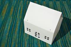 Weißes cardbox Haus mit Tür und zwei Fenstern Lizenzfreie Stockfotografie