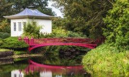 Weißes chinesisches Haus und rote Eisenbrücke Stockfotografie