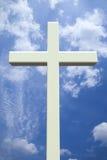 Weißes christliches Kreuz vor einem bewölkten Himmel Lizenzfreie Stockfotografie